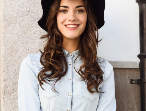 Portrait of young woman in urban background wearing casual clothes and hat